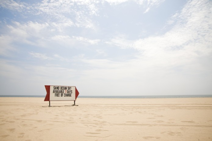 "An retro roadside sign on a beach that reads ""SAND OCEAN SKY, AVAILABLE 7 DAYS, FREE OF CHARGE"""